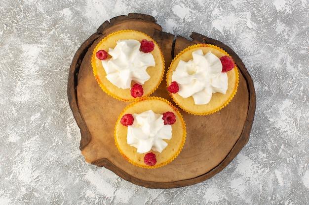 Tortas de vista superior con crema deliciosa horneada diseñada con frambuesa sobre el fondo gris crema de galletas dulces de azúcar
