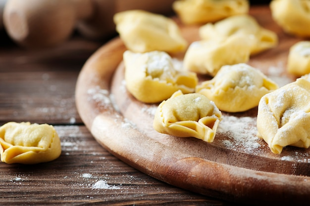 Tortellini casero italiano tradicional en la mesa de madera, enfoque selectivo