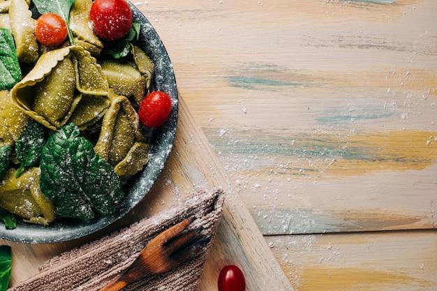 Tortellini de espinacas en una vieja mesa de madera rodeada de ingredientes frescos: tomate, harina, espinacas, huevos. comida vegana. copyspace