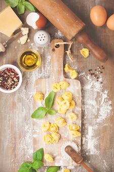 Tortellini de pasta italiana cruda sobre tabla de madera