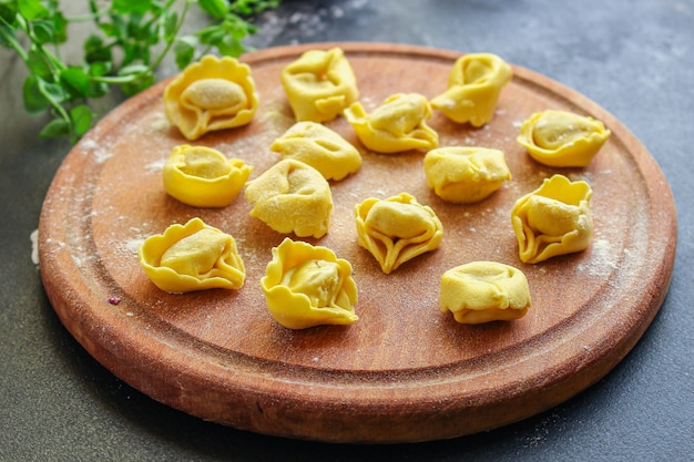 Tortellini pasta ravioles rellenos sobre tabla de madera