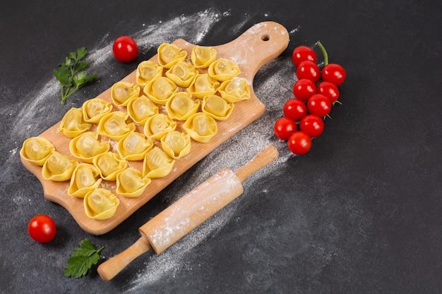Tortelloni crudo con relleno de champiñones sobre una tabla de madera
