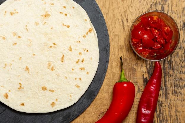 Tortilla cerca de pimiento y rodajas de tomate