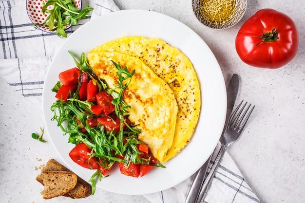 Tortilla clásica con queso y ensalada de los tomates en la placa blanca, visión superior.