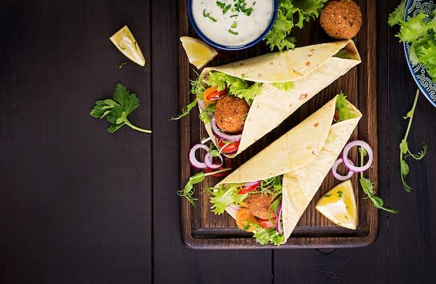 Tortilla envuelta con falafel y ensalada fresca. tacos veganos. comida vegetariana saludable. vista superior