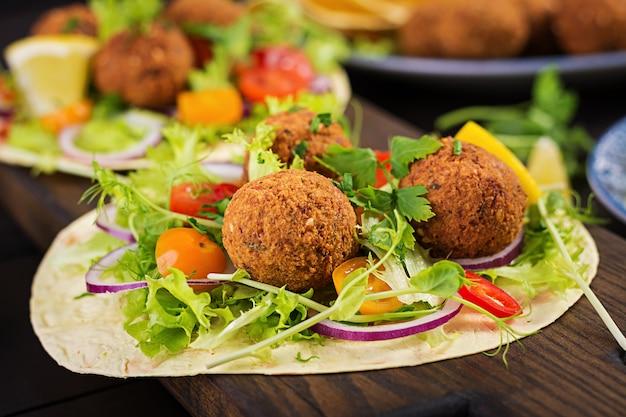 Tortilla envuelta con falafel y ensalada fresca. tacos veganos. comida vegetariana saludable.