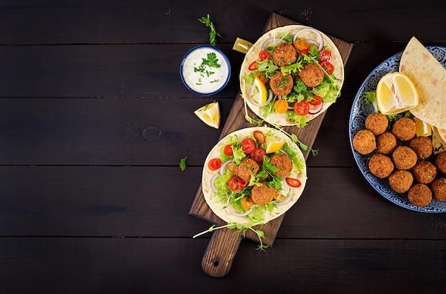 Tortilla envuelta con falafel y ensalada fresca.