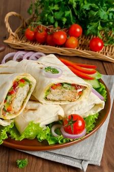 Tortilla fresca envuelta con kebab y verduras frescas en placa