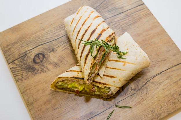 Tortilla fresca envuelta con pollo y verduras frescas en placa de madera