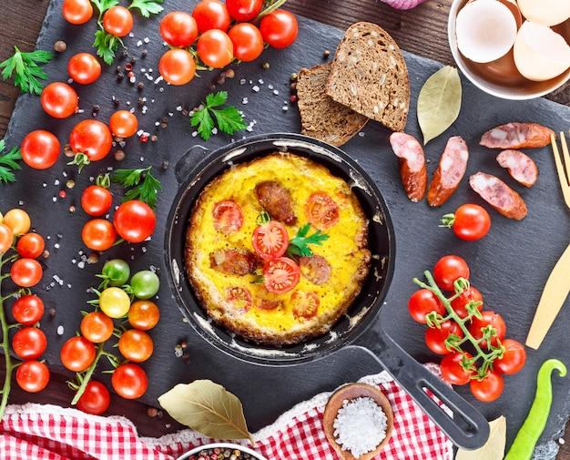 Tortilla frita de huevos de gallina con tomates cherry rojos