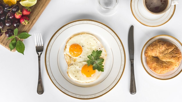 Tortilla frita con pan y frutas desayuno sobre el fondo blanco