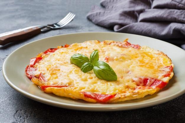 Tortilla, huevos revueltos con tomate y queso en un plato sobre una mesa oscura.