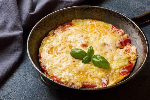 Tortilla, huevos revueltos con tomate y queso en una sartén sobre una mesa oscura.