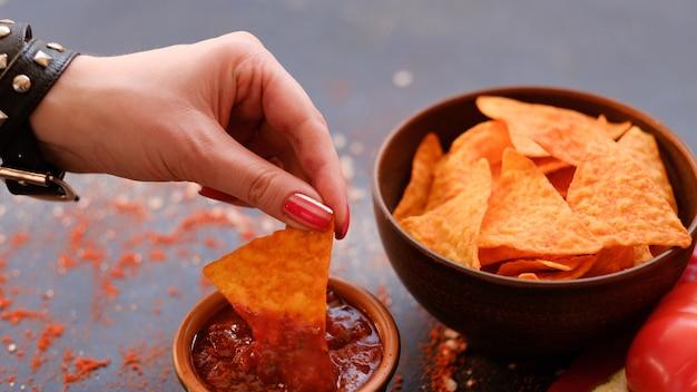 Tortilla nacho chips en un bol. delicioso cazador de cerveza. la mejor comida para un refrigerio rápido. mujer mano mojando crujientes patatas fritas triangulares picantes en salsa salsa