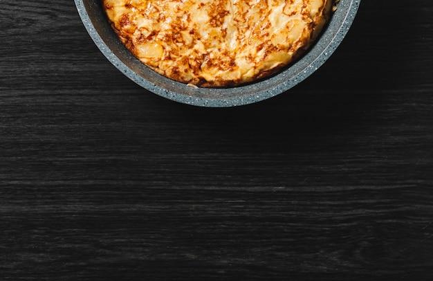 Tortilla de patatas en madera oscura, plato típico español.