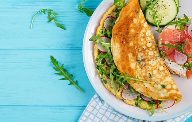 Tortilla con rábano, rúcula verde y sandwich con salmón en plato blanco