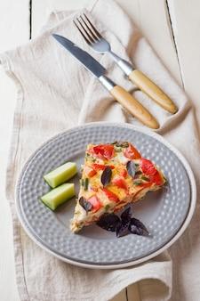 Tortilla de servir con verduras en un plato en una mesa de madera blanca