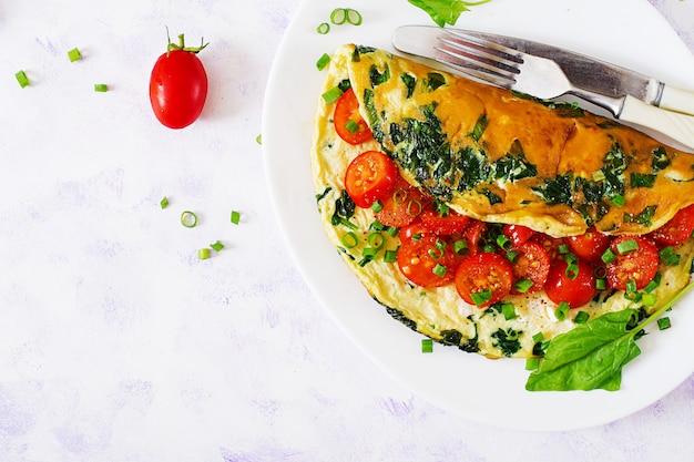 Tortilla con tomate, espinacas y cebolla verde en plato blanco.