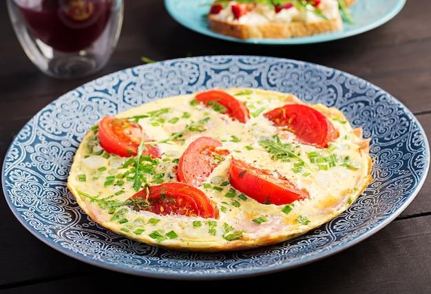 Tortilla con tomate, jamón y cebolla verde en mesa oscura