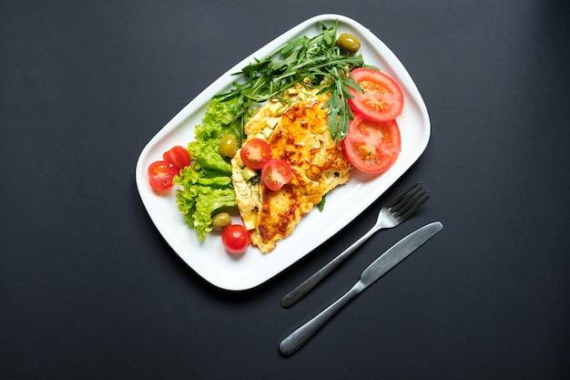 Tortilla de tomate servida con ensalada fresca. fondo negro