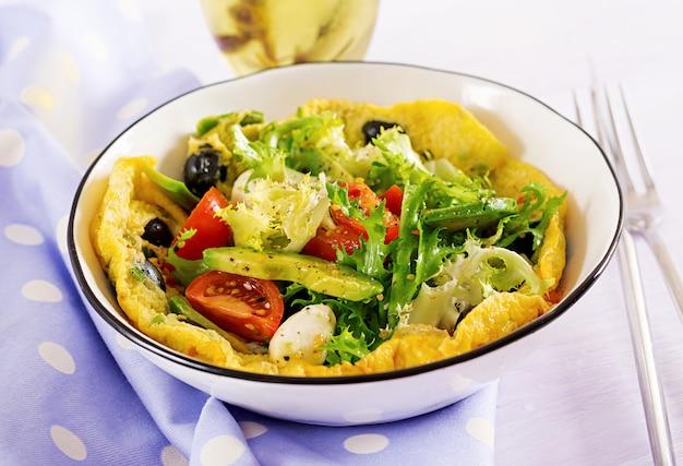 Tortilla con tomates frescos, aceituna negra, aguacate y queso mozzarella.