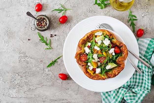 Tortilla con tomates frescos, aguacate y queso mozzarella. ensalada de tortilla. desayuno.