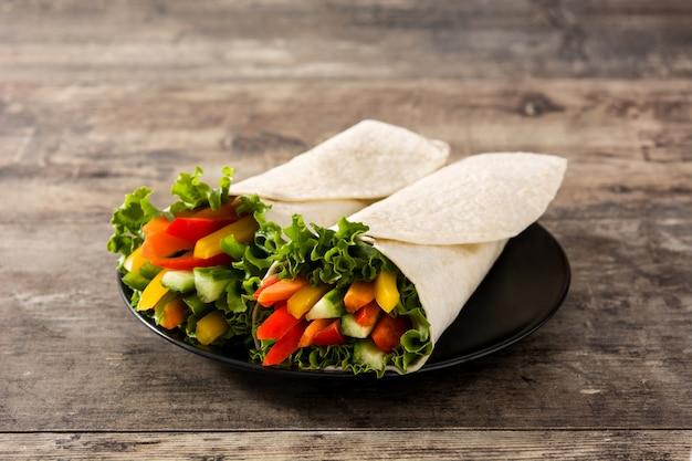 Tortilla de verduras envuelve en mesa de madera.