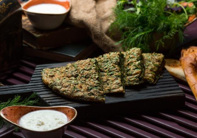 Tortilla de verduras, kuku, pizza en rodajas y servida sobre una tabla de piedra.