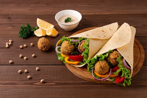 Tortillas envueltas con bolas de falafel y verduras frescas vegetarianas sobre un fondo de madera