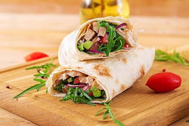 Tortillas envueltas con pollo y verduras en la superficie de madera. burrito de pollo. comida sana.