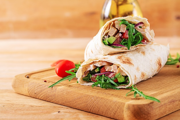 Las tortillas envuelven con el pollo y las verduras en fondo de madera. burrito de pollo. comida sana.