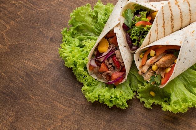 Tortillas frescas de primer plano envueltas con verduras y carne
