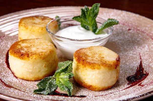 Tortita de queso, tartas de queso con crema agria, mermelada y menta en un plato. desayuno por la mañana.