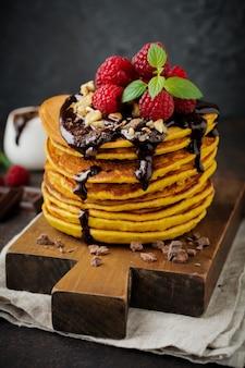 Tortitas de calabaza con frambuesas frescas, chocolate y nueces sobre piedra oscura o mesa de hormigón.
