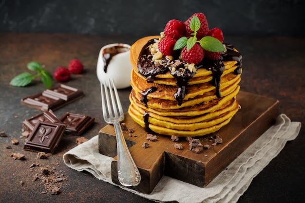 Tortitas de calabaza con frambuesas frescas, chocolate y nueces sobre piedra oscura u hormigón.