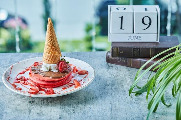 Tortitas con fresa, cono de helado en la placa blanca.
