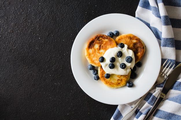 Tortitas de queso para el desayuno con crema agria o yogur y arándanos.