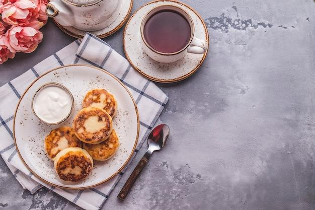 Tortitas de requesón con crema agria. concepto de desayuno o almuerzo con espacio de copia. vista superior