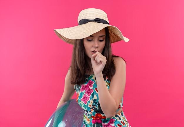Tos mujer joven con sombrero sosteniendo el anillo de natación y sosteniendo la mano en la boca en la pared rosa aislada