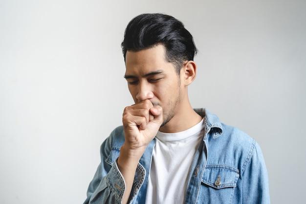 El toser asiático del hombre aislado en fondo en estudio.