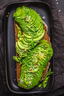 Tostada del aguacate con pan y semillas de centeno en la placa negra, fondo oscuro, visión superior.