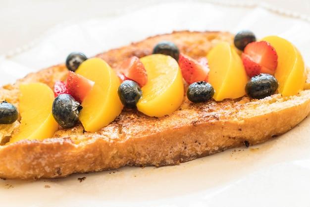 Tostada francesa con melocotón, fresa y arándanos