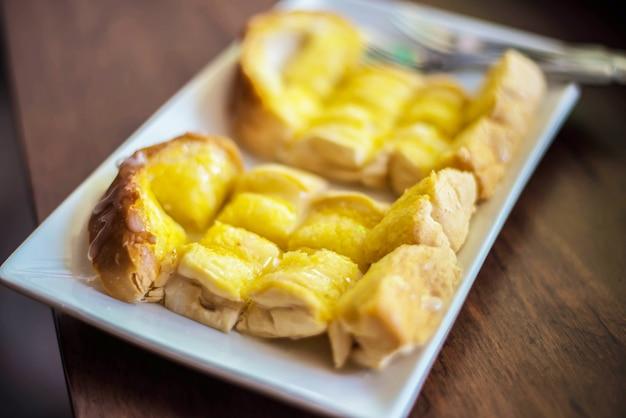 Tostada con mantequilla en la mesa de madera en el café.