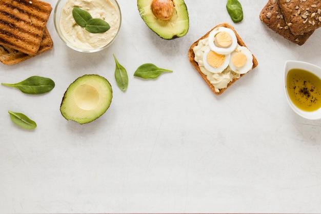 Tostada plana con huevos de hummus y aguacate con espacio de copia