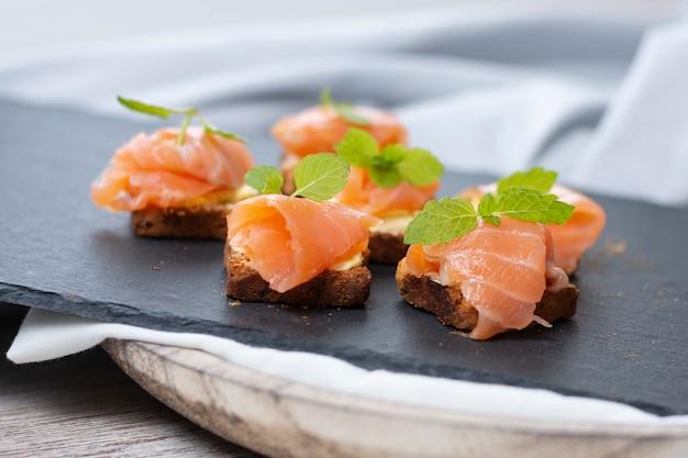 Tostada de salmón ahumado con hoja de menta en piedra negra y tabla de madera vieja