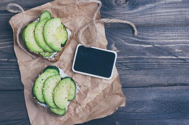 Tostada saludable con requesón, pepino verde y aguacate.