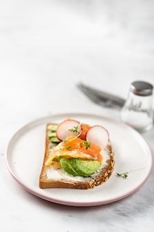 Tostada vegetariana con aguacate, rábano y salmón. alimentación saludable