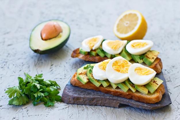 Tostadas con aguacate, limón, chile o paprika y huevos sobre un fondo gris