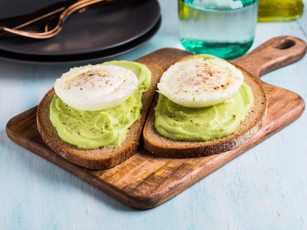 Tostadas del aguacate del pan de centeno con el huevo escalfado en tablero de madera de la porción. almuerzo brunch