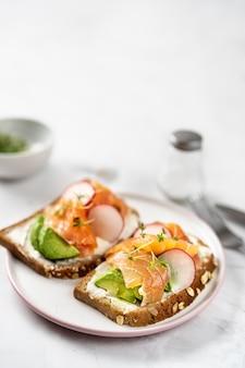 Tostadas con aguacate, rábano y salmón. alimentación saludable